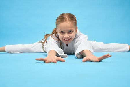Pretty, happy girl in white kimono training, making twine on blue background. Young, smiling, positive child lying and stretching hands, looking at camera, Kid performing exercises of japanese arts.