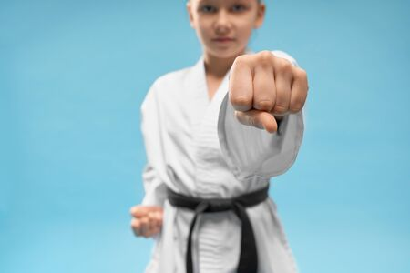 Close up of first, position of karate. Confident junior practicing punching. Young girl in white kimono with black belt posing on blue background in studio.