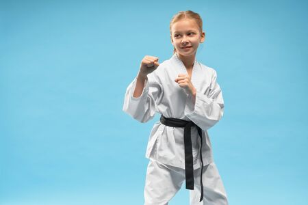 Happy girl standing in defense position. Pretty, confident karate child practicing combat sports. Cheerful junior posing in white kimono with black belt in studio on blue background. Фото со стока