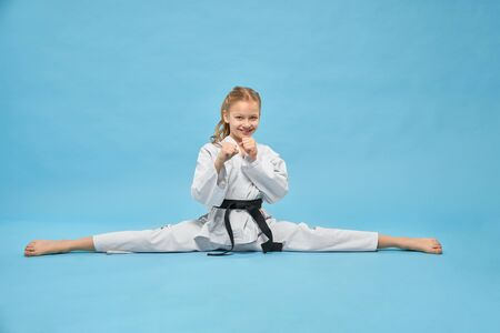 Karate girl in white kimono with black belt training, looking at camera and smiling. Positive, pretty child, making twine, sitting in combat position posing on blue background.