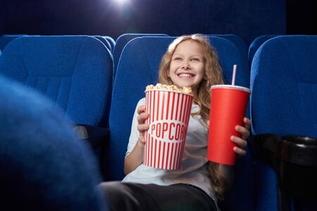 Selective focus of smiling girl keeping tasty popcorn and aerated sweet water while watching comedy in cinema. Happy female child enjoying funny movie. Concept of entertainment and fun.