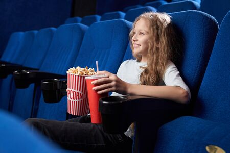 Side view of pretty female teen eating delicious popcorn, drinking aerated sweet water in cinema. Smiling girl sitting alone in hall and watching comical movie. Concept of entertainment. 스톡 콘텐츠