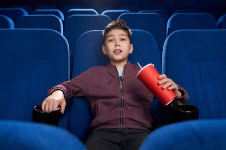 Selective focus of strained boy watching horror movie in cinema. Afraid teen drinking aerated sweet water and watching frightful film in movie house. Concept of unexpectedness and fun.