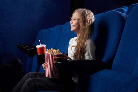 Funny female child sitting in hall of cinema, keeping tasty popcorn and laughing at comical film. Pretty girl resting and having fun on weekends. Concept of leisure and entertainment.