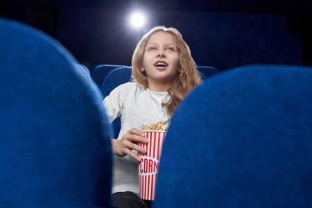 Selective focus of excited little blonde watching amazing movie in cinema. Cheerful girl keeping tasty cheese popcorn and enjoying interesting film. Concept of fun and entertainment.