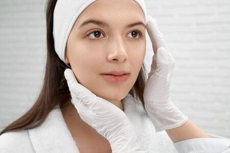 Manos de cosmetóloga en guantes médicos de goma blanca tocando e inspeccionando la cara del paciente joven y hermoso en el gabinete cosmético. Mujer en bata de baño blanca mirando hacia arriba. Concepto de cuidado de la piel. Foto de archivo