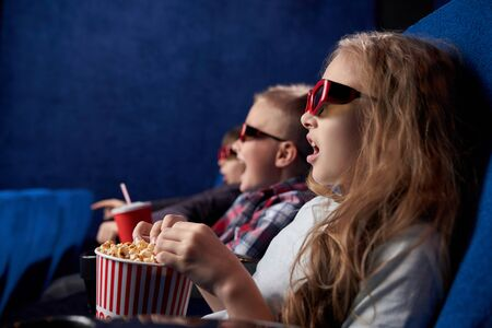 Shocked girl with opened eyes watching amazing film in movie house. Excited children wearing 3d glasses sitting together, eating tasty popcorn in cinema. Concept of leisure and fun.