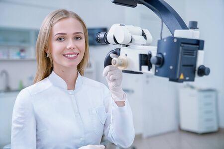 Entzückende blonde Frau, die als Stomatologe in einer privaten Zahnklinik arbeitet. Fröhlicher Zahnarzt, der in die Kamera schaut, lächelt und posiert. Spezialist, der mit modernen Geräten wie Dentalmikroskop arbeitet.