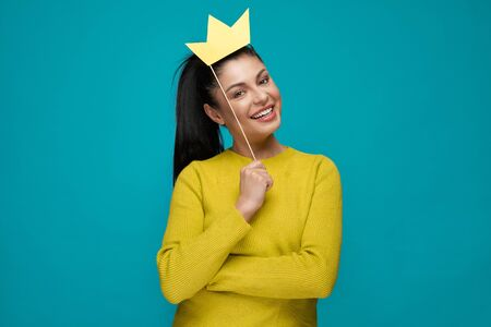 Young woman keeping paper crown and posing on blue isolated background. Beautiful brunette wearing yellow sweater looking at camera and laughing. Concept of happiness and entertainment.