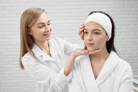 Young professional beautician with pleasure examining face of patient. Pretty positive woman in white bathrobe with well groomed skin looking away. Concept of health and beauty. 版權商用圖片