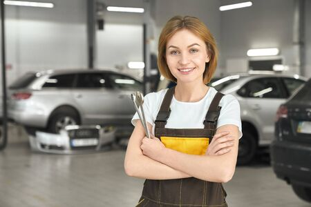 Handsome, charming woman smiling, looking at camera and holding tools, wrenches in hands. Female mechanic wearing in white t shirt and brown coveralls. Modern, professional autoservice.