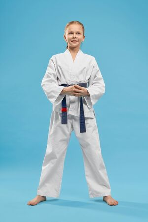Positive, cheerful girl standing in stance of karate on light blue background, looking up. Portrait of pretty junior wearing in white kimono with blue belt in studio. Concept of health and sport.