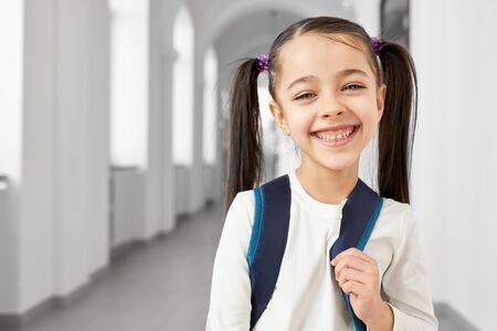 Cute, pretty, happy schoolgirl with hair tails standing in long, light hallway of primary school smiling, looking at camera. Beautiful, positive pupil with school backpack. Stock Photo