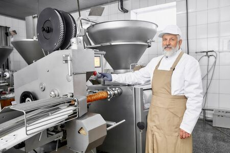 Elderly man working on sausage production. Professional worker wearing in uniform standing near equipment, posing and looking at camera. Butcher working at modern factory.
