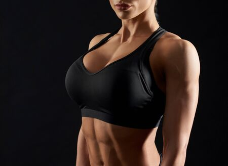 Young, gorgeous woman with beutiful breats wearing in black sportswear, posing in studio. Attractive, sexy, female, muscular body in black top on black background.