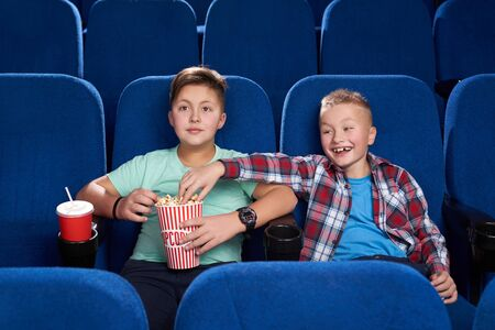 Front view of cunning boy stealing popcorn while male friend watching interesting film in cinema. Happy children eating junk food, drinking sweet water and having fun on weekends. Concept of fun.