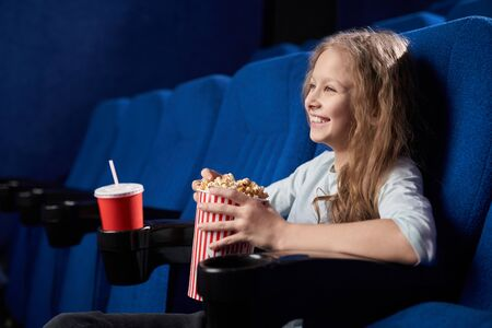 Side view of cheerful long haired girl laughing at funny comedy in cinema. Happy female child eating popcorn, drinking aerated sweet water and relaxing on weekends. Concept of entertainment. 스톡 콘텐츠