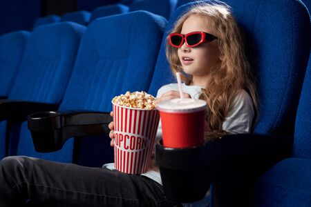 Pretty girl wearing 3d glasses sitting on comfortable seat, keeping popcorn and drinking sweet water in cinema. Excited child captured with interesting film in movie house. Concept of entertainment.