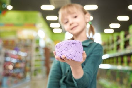 Close up of kinetic sand child showing on hand. Young, pretty girl holding violet kinetic sand, looking at camera and posing in toy store. Shelves with goods on background.