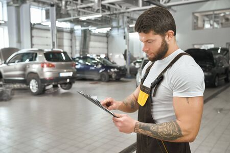 Handsome, muscular mechanic holding folder, reading. Bearded man with tattoed hands wearing in coveralls and white t shirt. Repairman working in autoservice. Stock Photo