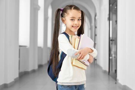Pretty, cheerful schoolgirl with school backpack standing in long hallway of primary school, holding books. Beautiful, cute child with two hair tails looking at camera, smiling.