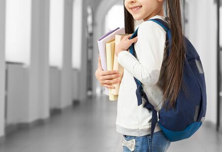 Cute, little schoolgirl standing in long school hallway, holding books. Pretty, positive child with long hair in white sweatshirts and jeans. Concept of study and education.