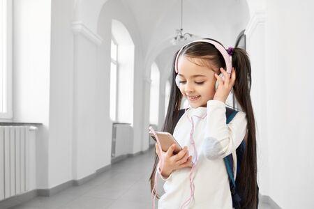 Pretty, funny schoolgirl in white sweatshirt with headphones holding pink phone. Happy, beautiful schoolchild of primary school standing in hallway, looking at phone.