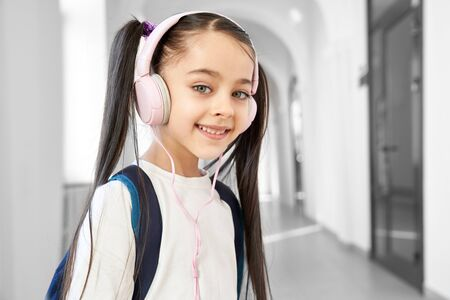 Pretty, positive schoolgirl standing in hallway of primary school. Cute child with long hair in tails and headphones listening music, smiling, looking at camera.