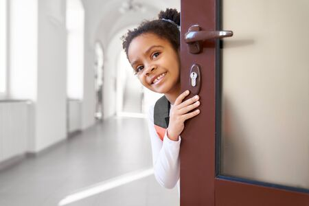 Pretty, positive, beautiful schoolgirl peeking from classroom door, smiling. Cute, cheerful child of primary school with dark curly hair looking at camera. Stock Photo