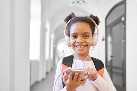 Pretty, positive schoolgirl with headphones holding phone, posing, looking at camera. Happy, beautiful child standing in long hallway, listening musik and smiling. Stock Photo