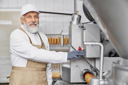 Butcher man working on sausage and meat production. Professional worker in white uniform standing near new modern equipment, posing and looking at camera. Stock Photo