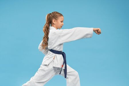 Pretty, confident junior standing in stance, practicing of punching. Karate girl wearing in white kimono with blue belt training. Child posing in studio on light blue background.