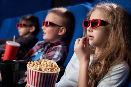 View from side of shocked girl wearing 3d glasses eating popcorn and watching fantasy in cinema. long haired female child resting with friends and having fun on weekends. Concept of leisure.