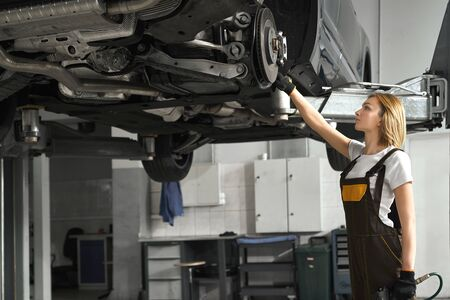 Beautiful young woman standing near lifted vehicle, observing and fixing brake discs with special tool. Girl wearing in white t shirt and coveralls, working in autoservice station.