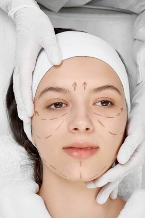 Close up of young female face with black lines. Professional cosmetologist with surgical marks indicating line of correction. Hands of doctor in white rubber gloves touching face of client. 스톡 콘텐츠