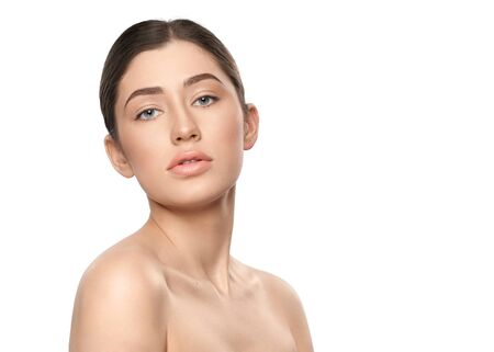 Front view of sensual woman without makeup posing on white isolated background. Attractive sexy lady with plump lips looking aside in studio. Concept of rejuvenation and cosmetology.