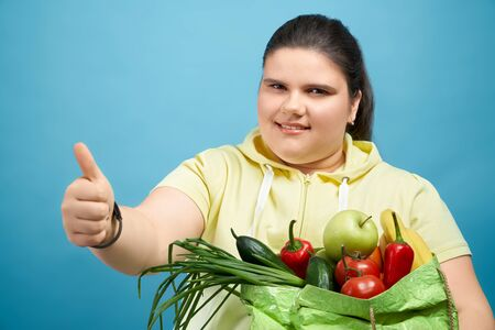 Side of pretty fat girl in yellow sweater with package of fresh fruits and vegetables showing thumb up, smiling and looking at camera.Young female is choosing healthy food and showing it by sign super