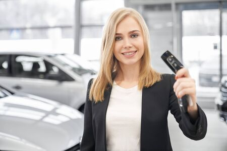 Front view of pleasant female car dealer in white shirt and black suit keeping car keys at hands in auto show room. Woman looking at camera, smiling and showing keys. Concept of car selling.