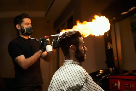 Professional handsome barber with black mask on mouth is going to make a haircut with fire treatment to male bearded client that is sitting in chair and covered by striped cape at modern barbershop