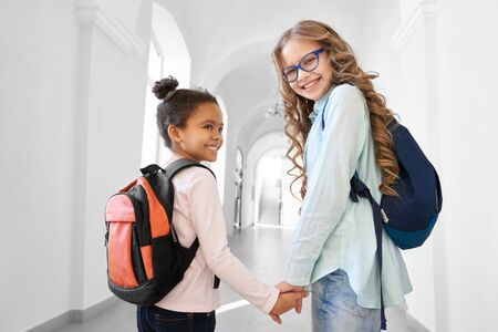 Two pretty school girls blonde Caucasian and brunette African holding each other by hands and smiling, going to lesson. Funny girls friends with deference in age spending time together.