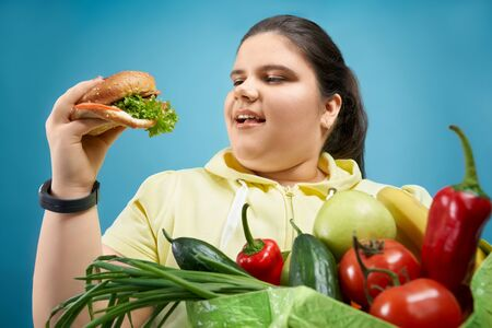 Portrait of overweight girl that is pretending to eat burger but not fresh fruits and vegetables that are holding on green package. Happy female with open mouse is looking at fastfood oh her hand Reklamní fotografie