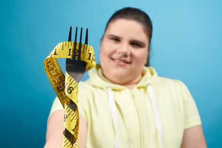 Close up of fork that is wrapped by measuring tape which is holding young overweight brunette girl in yellow sweater. Pretty female is trying to control her dieting regime.