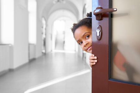 Pretty African girl hiding from opened door in school corridor , looking at camera. Little and cute pupil holding door , going to lesson at class room. Concept of break. Stockfoto
