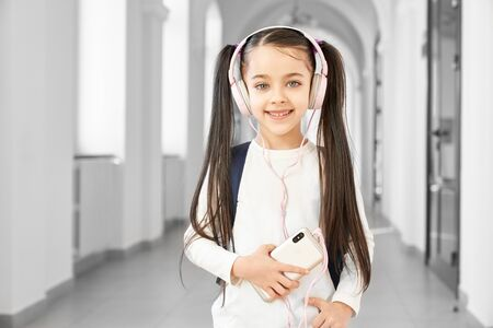 Portrait of pretty brunette school girl with funny hairstyle listening music on smart phone from big pink headphones. Smiling girl looking at camera, standing among corridor of beautiful school.