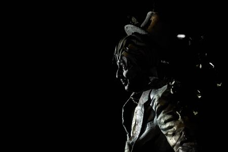 Side view of enigmatic mime dressed in strange black golden suit and wearing top hat on his head.Talented actor imitating some statue or fairy tale character on black background