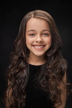 Front view of cheerful little girl looking at camera and laughing in studio. Beautiful long haired child smiling and posing on black isolated background. Concept pf beauty and happiness.