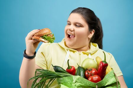 Oversized happy woman is going to enjoy fresh made burger while keeping big green package of fruits and vegetables on her hand. Concept of junk food that has bad influence on our body.