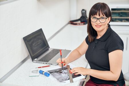 Professional female dentist in glasses posing while working with x ray picture of teeth in dental office. Woman looking at camera and smiling. Concept of medicine and modern technology.