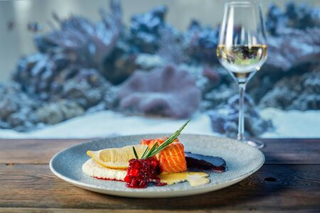 Delicious salmon steak with three kinds of sauces served on blue plate on wooden table in restaurant. Glass of white wine.
