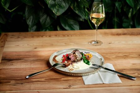 Delicious and tender roast duck with sauce served on plate with fork and knife in restaurant. Glass of white wine.